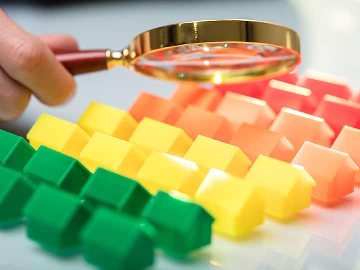 Miniaturhäuschen werden mit einer Lupe inspiziert.