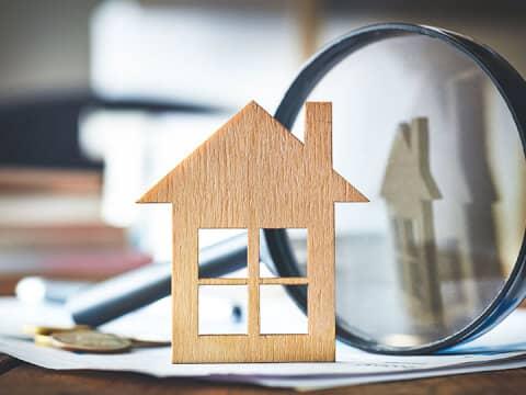 Auf einem Schreibtisch steht eine Holzschablone eines Hauses an eine große Lupe gelehnt.