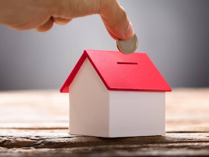 Eine Spardose, in Form eines weißen Hauses mit rotem Dach, in die gerade eine Münze geworfen wird.