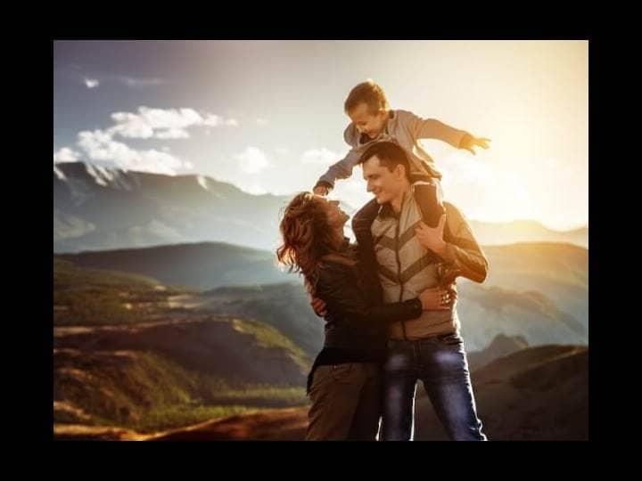 Ein Paar steht in einer schönen sonnigen Landschaft und lächelt sich an, der junge Sohn sitzt auf den Schultern des Vaters.