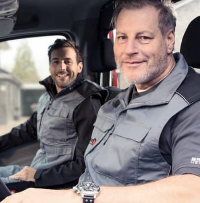 Zwei Brötje Mitarbeiter im Lieferwagen sitzend. Beide lächeln.