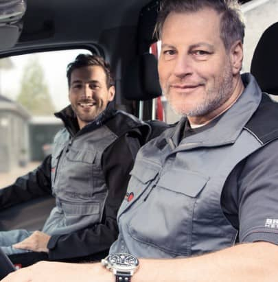 Two Brötje employees sitting in a delivery van. Both are smiling.